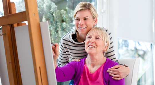 Caregiver and senior doing painting